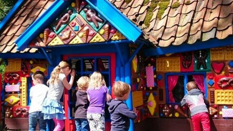 Kinderen gluren bij snoephuisje Hans en Grietje Sprookjesbos Valkenburg