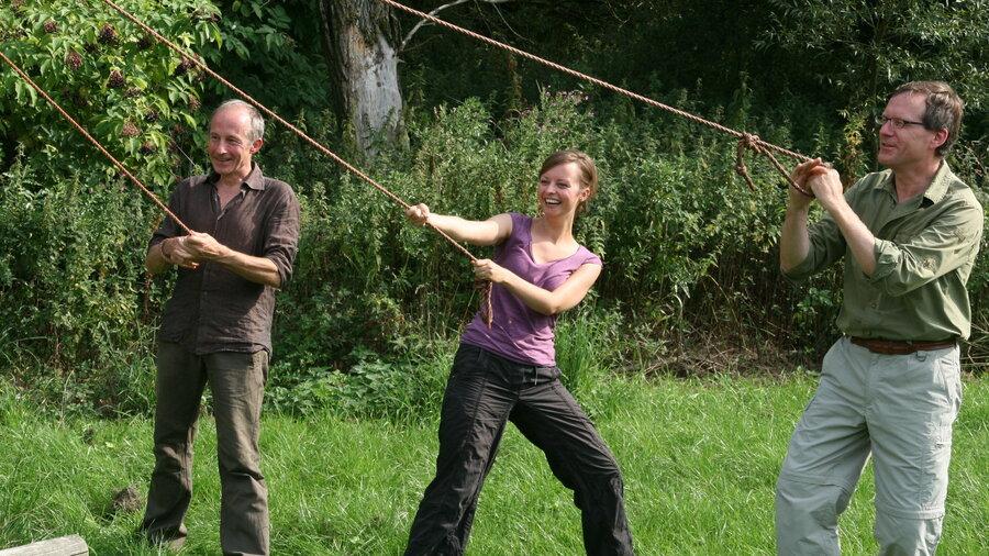 Twee mannen en een vrouw lachen tijdens touwtrekken bij de survival