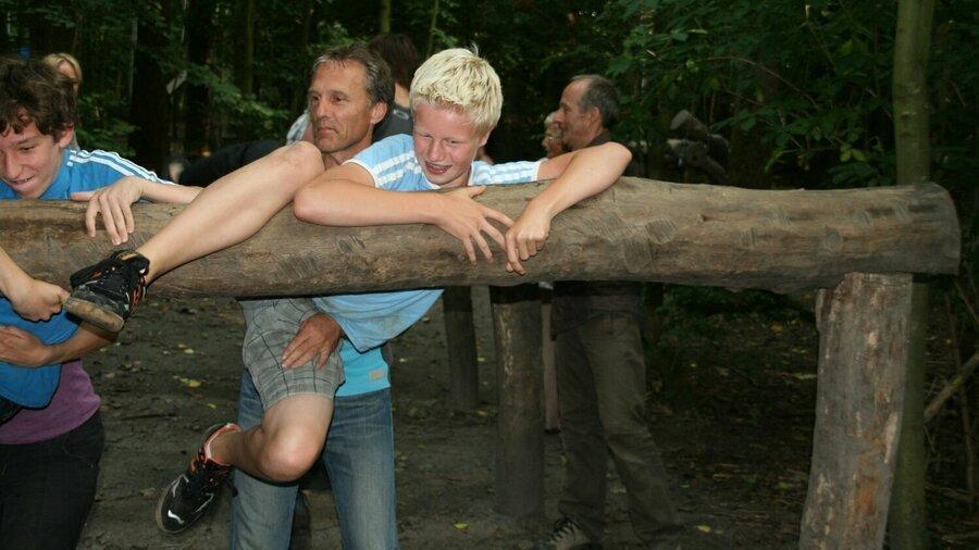 Vader helpt zoon over boomstam te klimmen