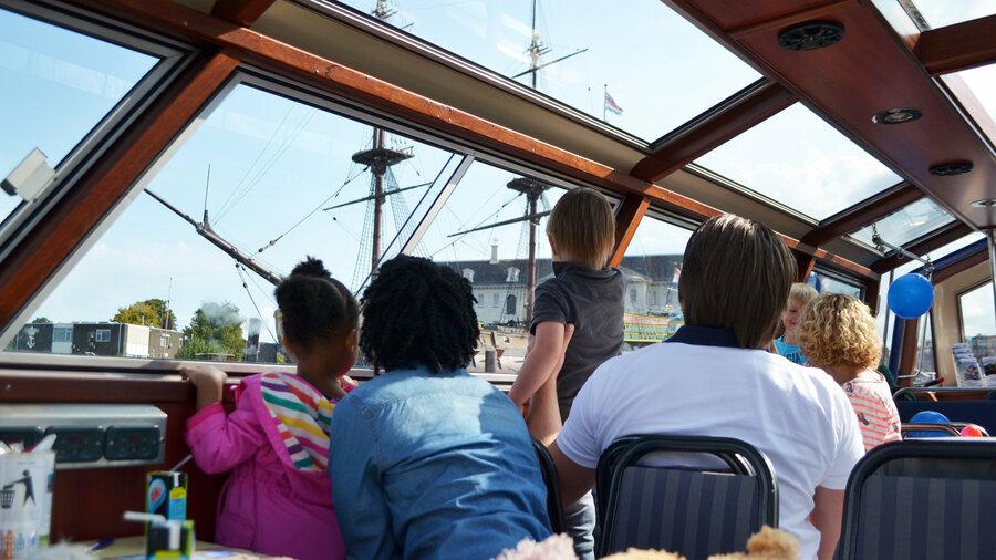 Gezin kijkt uit raam blue boat company rondvaart amsterdam