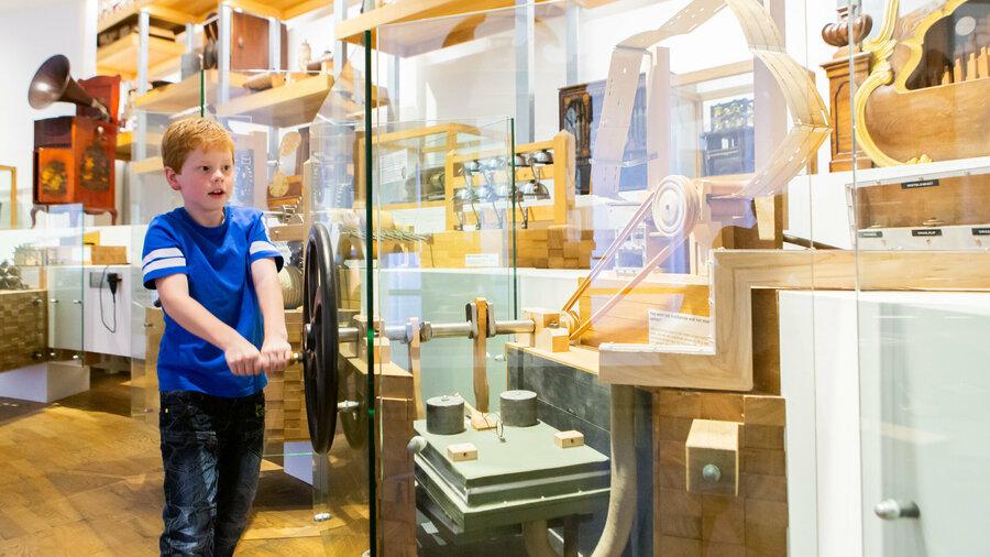 Jongetje speelt met muziekinstrument in Museum Speelklok