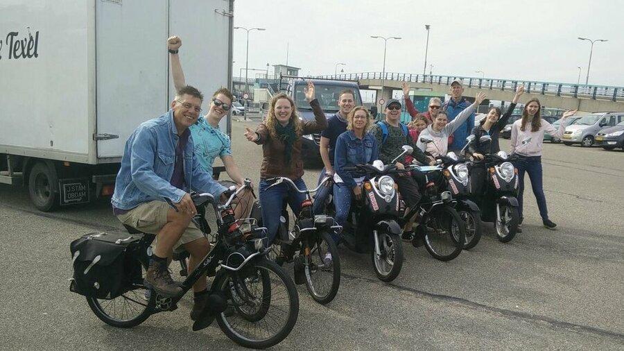 Groep mensen op een Solex in Texel