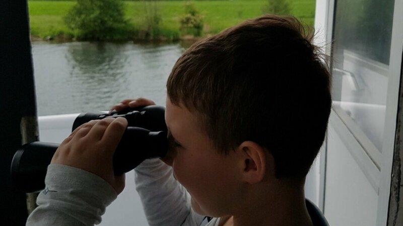 Jongen met verrekijker aan boord bij Rederij Cascade