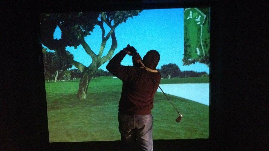Man golft voor een golfsimulator