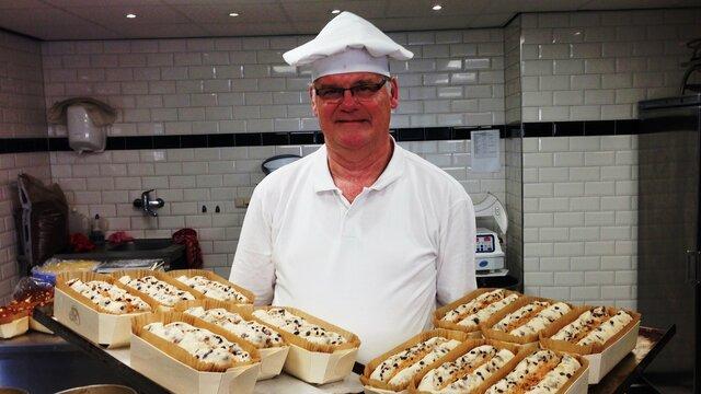 De bakker toont zijn broodjes op een dienblad