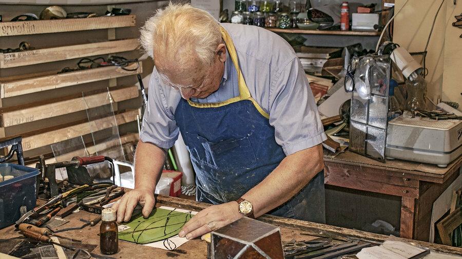 Meneer die een glas-in-lood-raam maakt