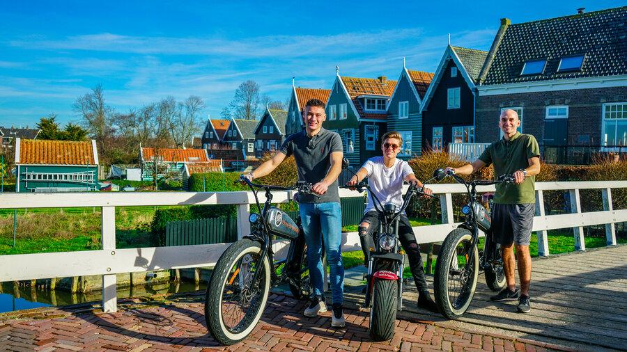 Mannen op scooters en e-fatbikes voor visserhuisjes