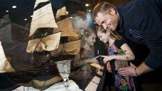 Vader en dochter kijken naar een modelschip in een vitrine