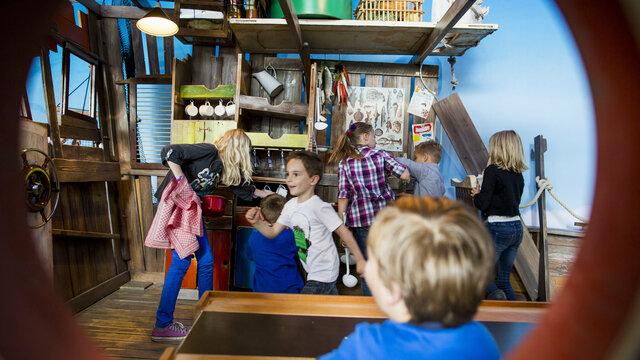 Blik vanuit een rond scheepsvenster op spelende kinderen