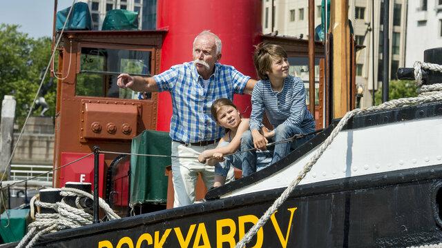 Een opa staat buiten met twee kleinkinderen op een schip bij het Maritiem Museum