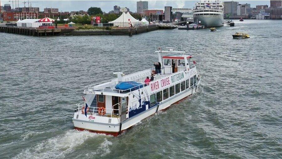 De boot van River Cruise Rotterdam in de Rotterdamse haven met de SS Rotterdam en een watertaxi.