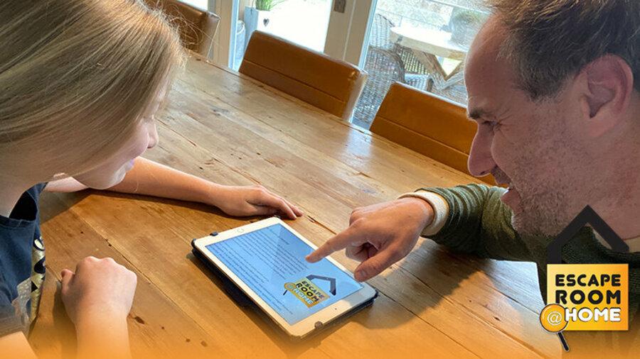 Dochter en vader spelen online escape game op tablet van Escape Room @ Home