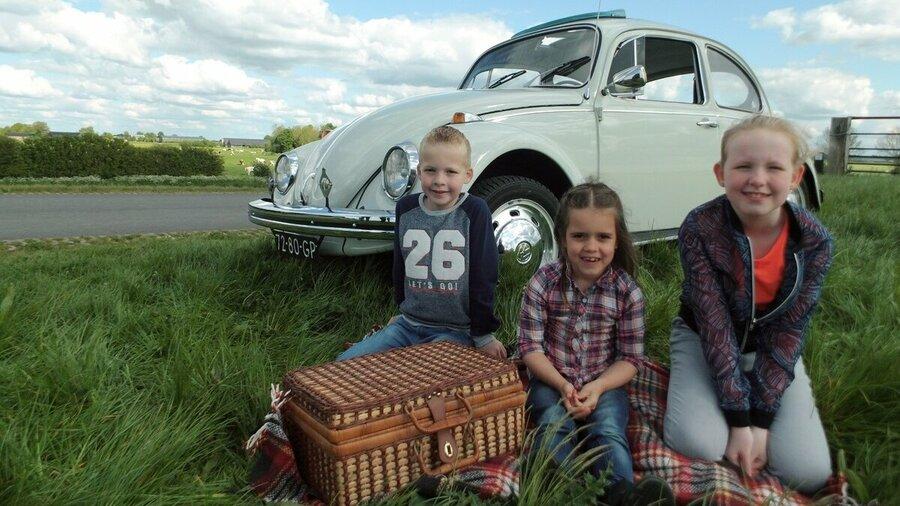 Gezin picknickt tijdens tour met Volkswagen Kever 1968 van Vintagecars Wapenveld