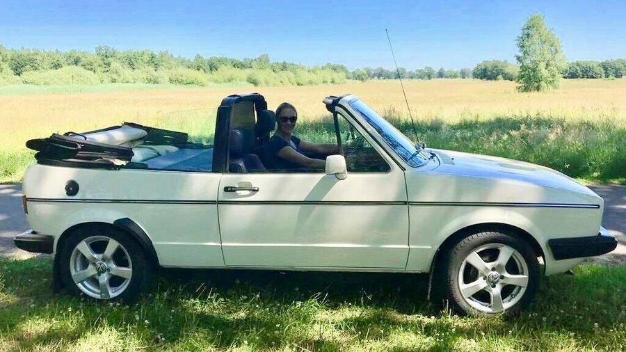 Vrouw met dak omlaag in Volkswagen Golf 1 Cabrio 1985 van Vintagecars Wapenveld