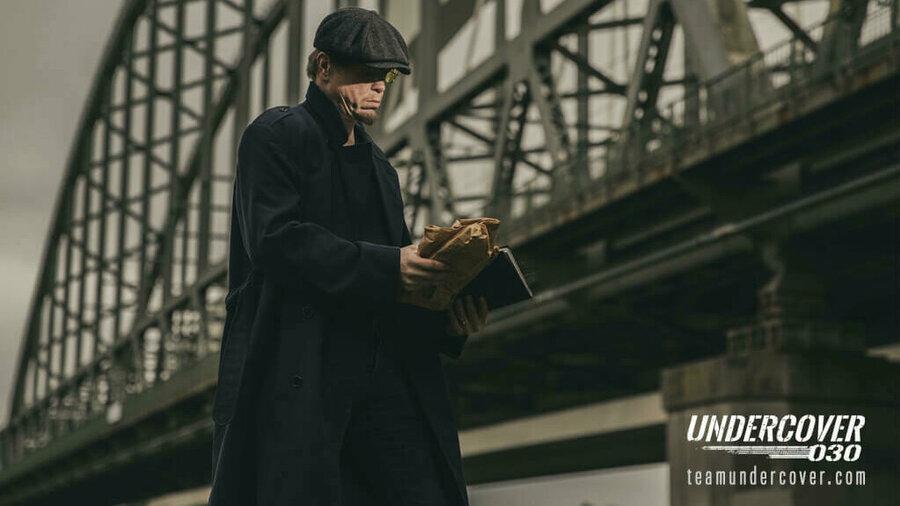 Undercover 030 - Man in pet en lange jas voor brug bestudeert boeken die hij vasthoudt.