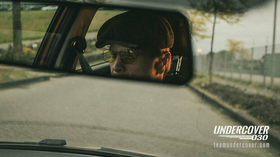 Undercover 030 - Blik door voorruit auto, via de achteruitkijkspiegel zie je een man met pet en bril.