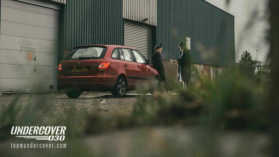 Undercover 030 - Twee mannen in gesprek bij een auto voor een gesloten bedrijfspand.
