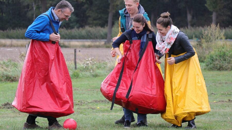 Vier mensen voetballen terwijl ze een soort zak aanhebben.