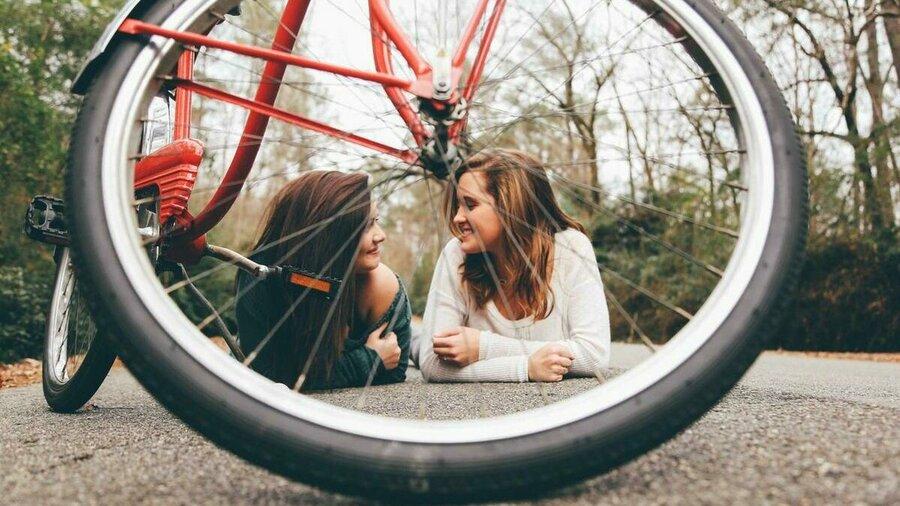Twee meiden die op de grond relaxen, gezien door het voorwiel van hun fiets.