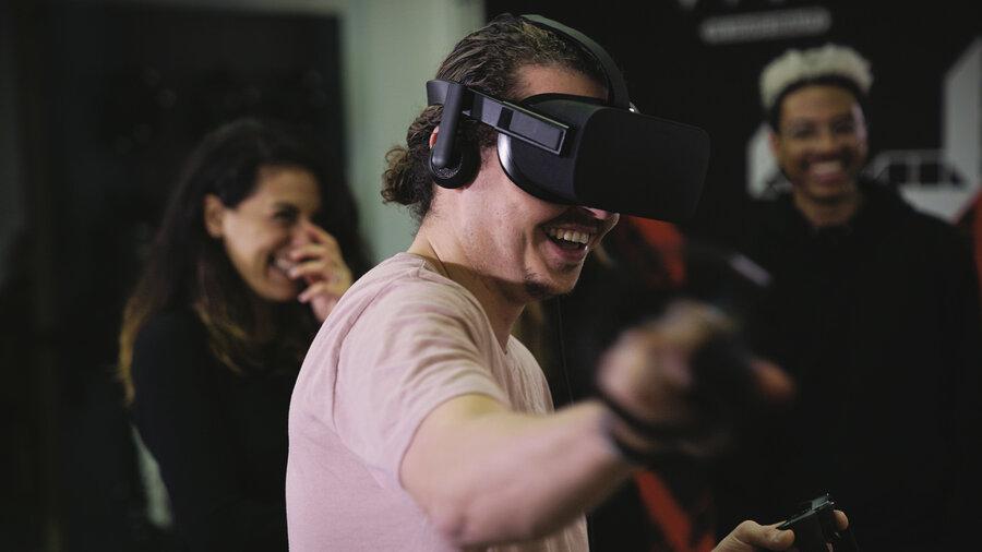 Man met met VR-bril op en control sticks, twee anderen kijken op de achtergrond toe.