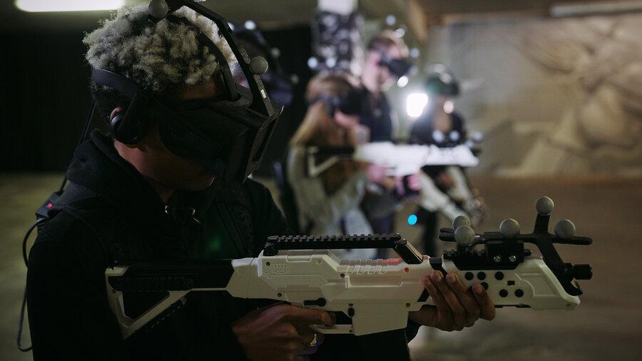 Een rij mensen speelt met VR-bril op een shootergame, de controls lijken op geweren.