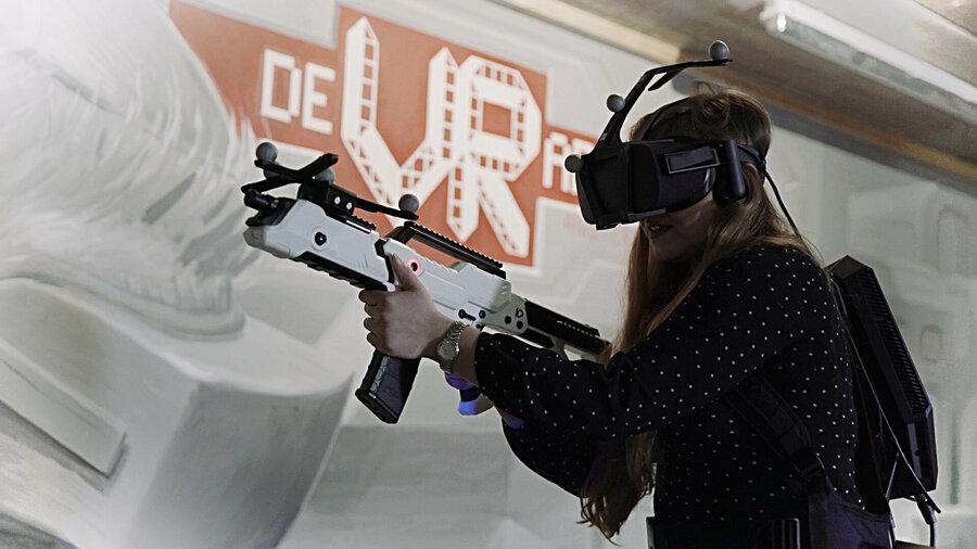 Een meisje met VR-uitrusting en een controller die lijkt op een geweer.