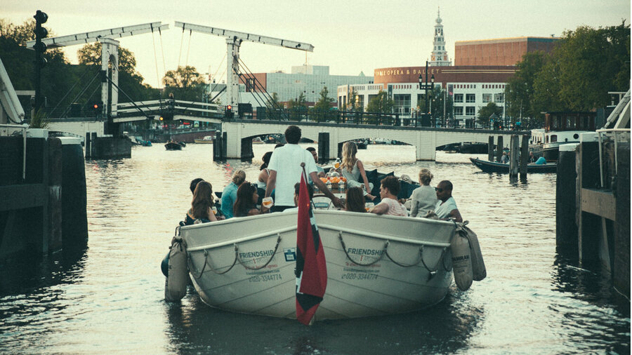 Open sloep van Friendship vaart een Amsterdamse gracht in.