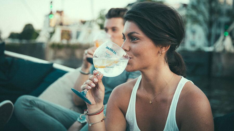 Een jonge vrouw en man genieten van een drankje in een open sloep van Friendship Amsterdam