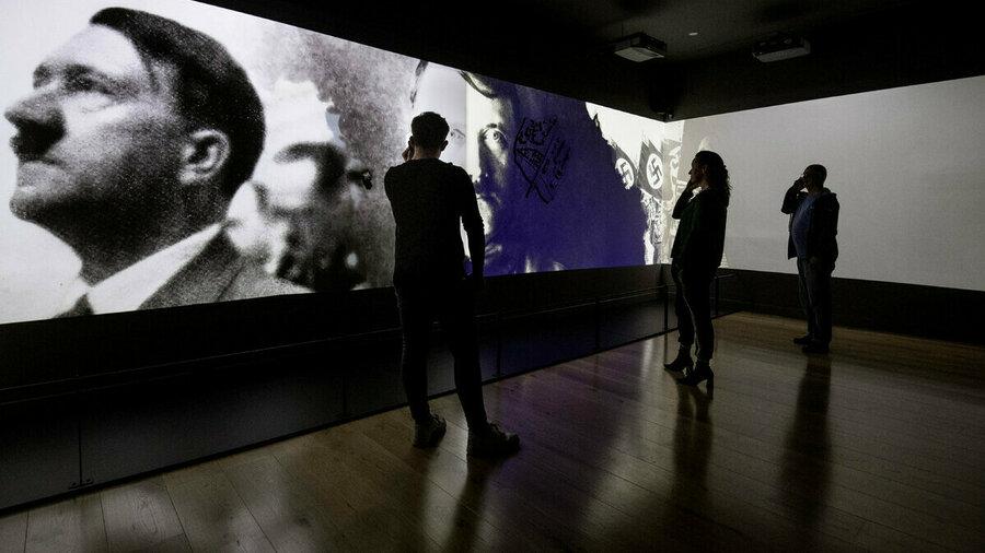 Mensen kijken met een audiotour aan hun oor naar beelden uit de Tweede Wereldoorlog