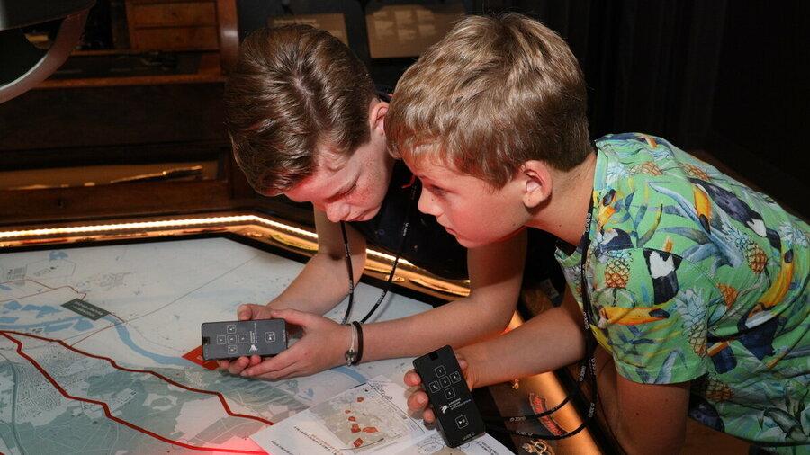 Twee jongens luisteren naar de kinderaudiotour van het Airborne Museum terwijl ze ook kaarten bekijken