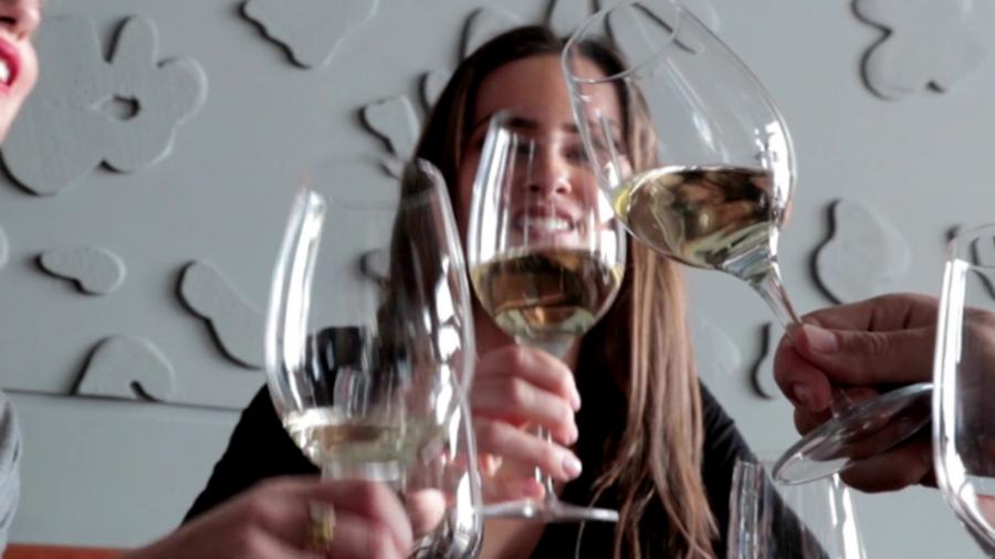 Drie mensen proosten met witte wijn in grote glazen.