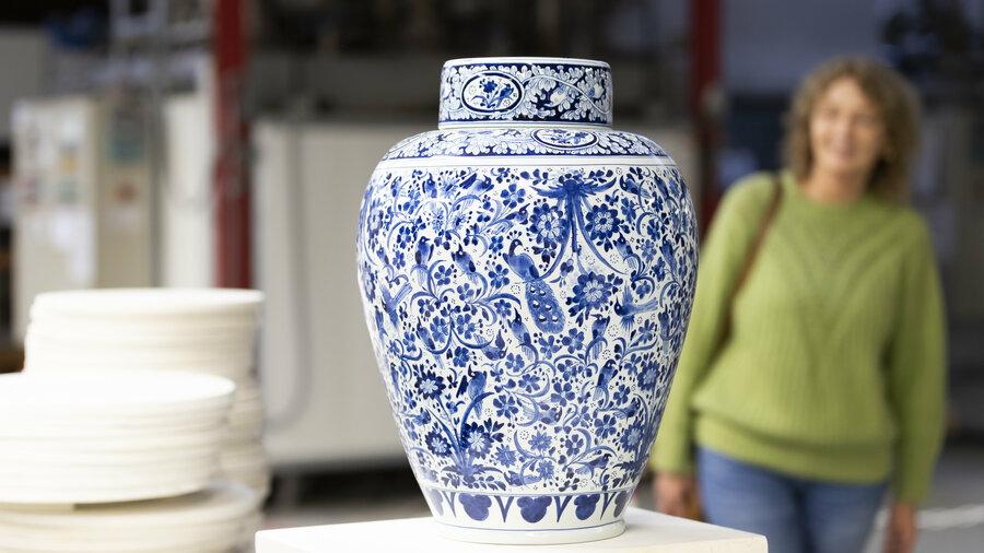 Grote Delfts blauwe vaas met op de achtergrond een vrouw die hem bekijkt bij Royal Delft Experience
