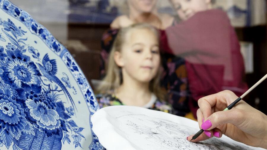 Meisje bekijkt hoe een bord van aardewerk wordt beschilderd bij Royal Delft Experience