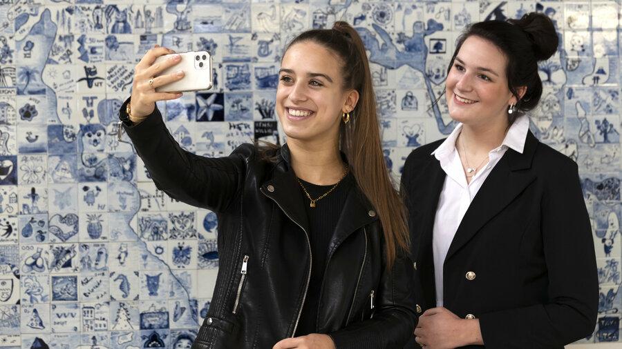 Twee meiden nemen een selfie voor een muur van Delfts blauwe tegeltjes bij de Royal Delft Experience