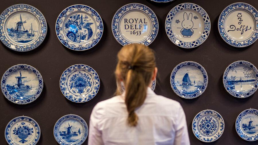 Een vrouw bekijkt een wand waarop borden van Delfts Blauw hangen bij de Royal Delft Experience