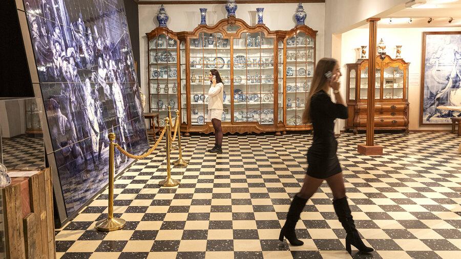 Twee vrouwen luisteren in een zaal van de Royal Delft Experience naar de gratis audiotour