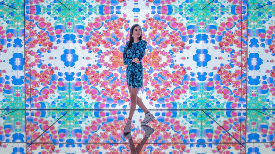 Vrouw met allemaal kleurige projecties om zich heen in het Moco Museum