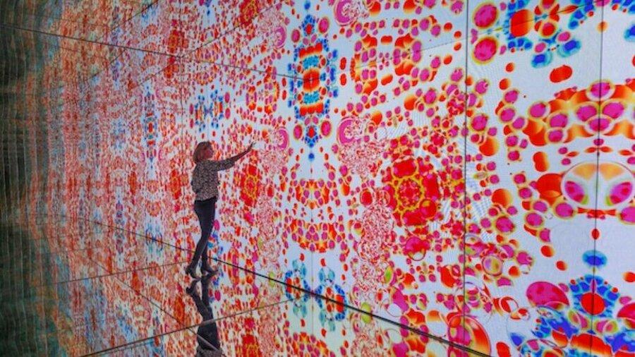 Vrou voor enorm virtueel kunstwerk in het Moco Museum