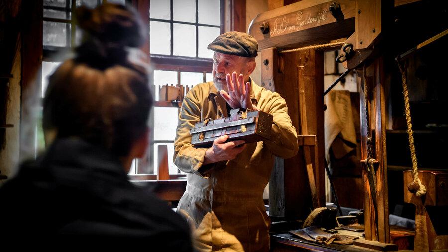 Vrouw luistert naar uitleg van een van de ambachtsmannen in het Nederlands Openluchtmuseum