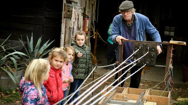 Vier kinderen zijn gefascineerd door het werk van de touwslager in het Nederlands Openluchtmuseum
