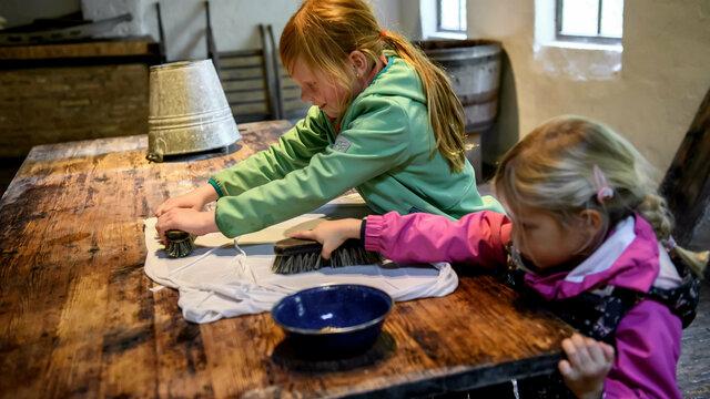 Twee kinderen schrobben de was schoon in het Nederlands Openluchtmuseum