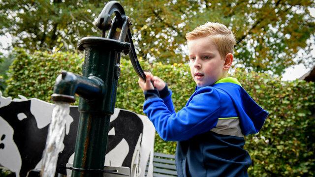 Jongen pompt water met de pomp op het Kindererf van het Nederlands Openluchtmuseum